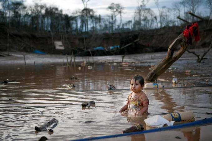 In this May 3, 2014 photo, Prisaida, 2, sits in the shallow waters of a polluted lagoon as her parents mine for gold nearby, in La Pampa in Peru's Madre de Dios region. The lagoon emerged as a result of miners bombarding the earth with jet streams of water in search of gold. The miners know they will be soon be evicted, Peru?s government declared all informal mining illegal on April 19. (AP Photo/Rodrigo Abd) ORG XMIT: ABD115