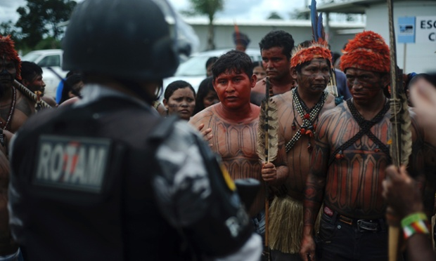 Indiginous people face police officers in Belo Monte