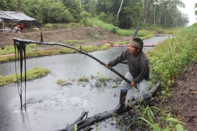 Pastor Dahua, president of the community of Monterrico, dips a stick into oil from a pipeline spill reported on September 25. Photo © Barbara Fraser.