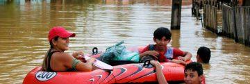 Família flutuando em bote durante cheia histórica de 2015 no Acre