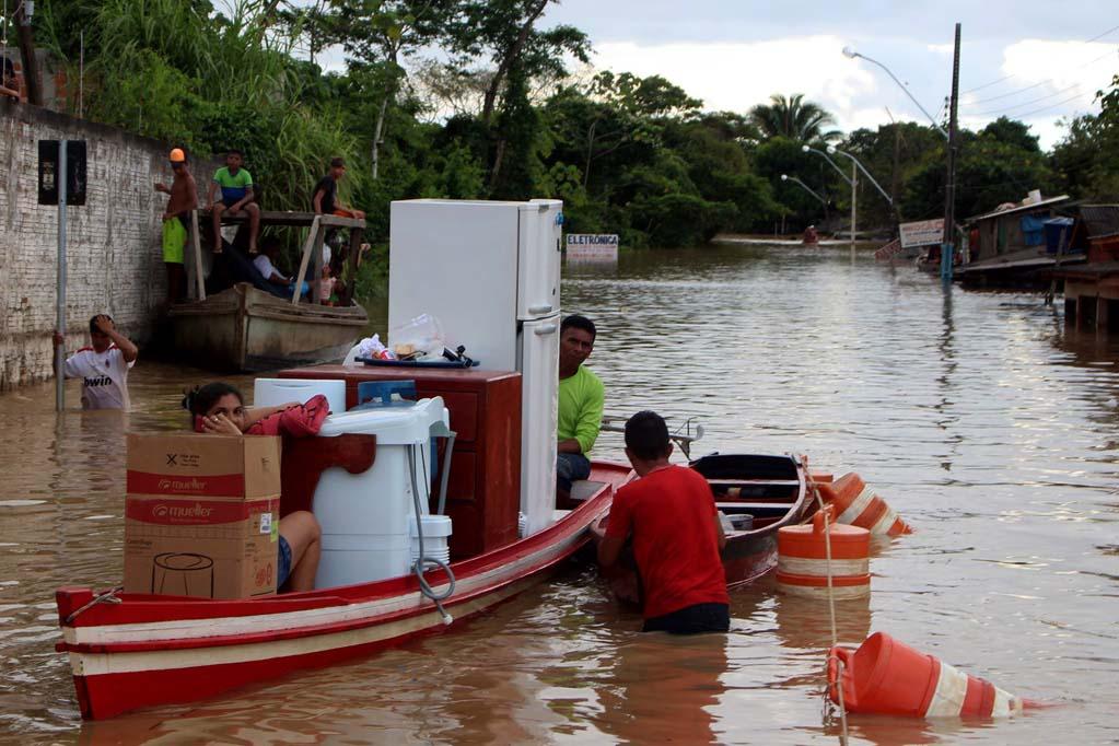 Família leva eletrodomésticos em barco na cheia histórica de 2015 no Acre