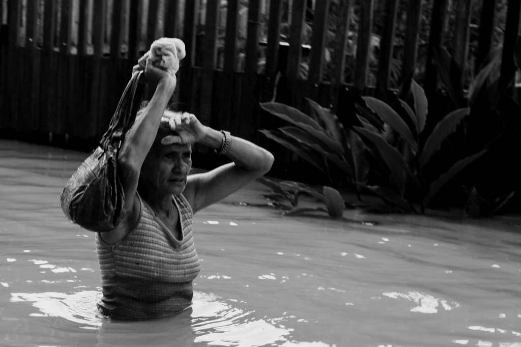 Mulher caminha com dificuldades durante cheia histórica de 2015 no Acre