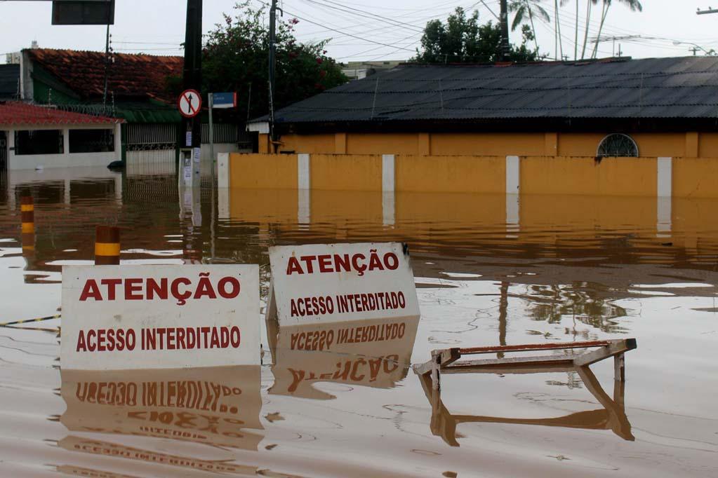 Placas de acesso interditado submersas em ruas alagadas durante cheia histórica de 2015 no Acre