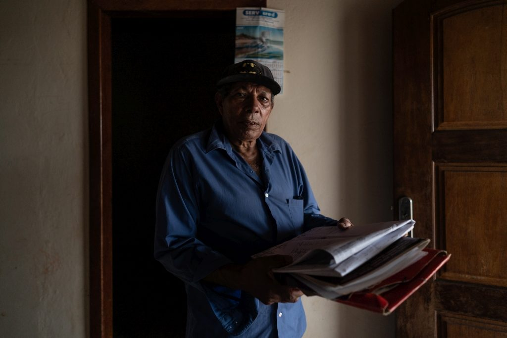 Nelson Bispo dos Santos, a man wearing a blue button down shirt and a hat, holds a stack of newspapers and other documents.