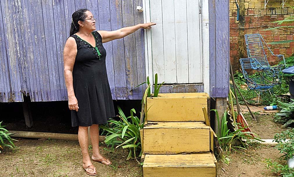 Maria de Jesus mostra a altura que a água alcançou em sua casa na última cheia. Foto: Maria Emília Coelho
