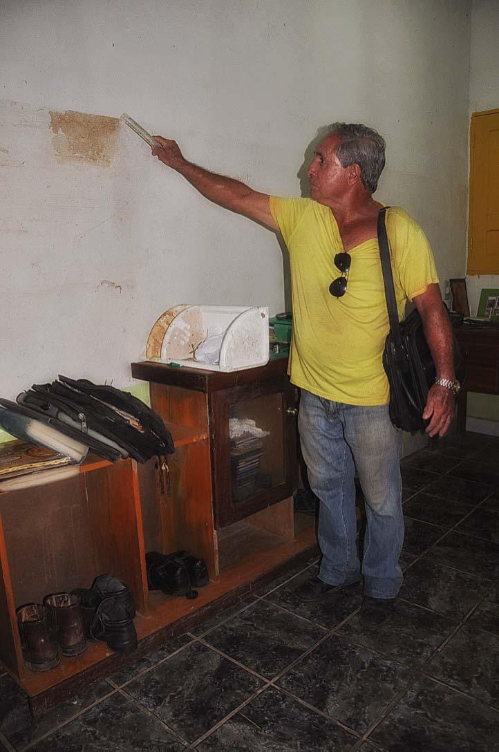 Otacílio Augusto de Oliveira aponta a marca da água em sua casa após a cheia de 2015 no Acre. Foto: Maria Emília Coelho